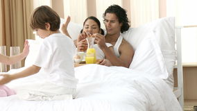 Parents having breakfast and children playing in bed. Footage in high definition