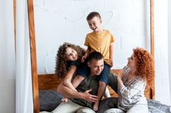 Parents having fun with their two little kids  on bed. Happy young family spending time together at the morning royalty free stock image