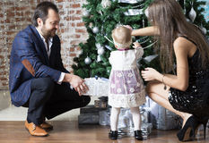 Parents help child to trim the tree. Royalty Free Stock Image