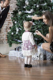 Parents help child to trim the tree. Stock Photos
