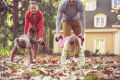 Parents help daughters walking on hands. Playful. On the move Stock Photography