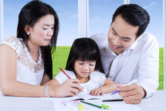 Parents help their child to write Royalty Free Stock Photo