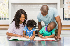 Parents helping children doing homework. In the kitchen Royalty Free Stock Images