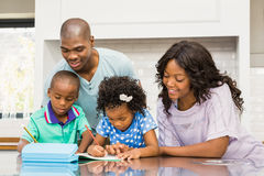 Parents helping children doing homework. In the kitchen Stock Photos