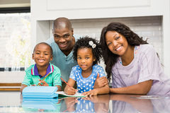 Parents helping children doing homework. In the kitchen Stock Photo