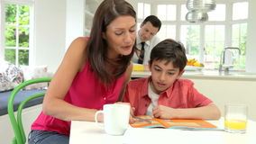 Parents Helping Children With Homework In Kitchen stock footage