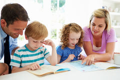 Parents Helping Children With Homework In Kitchen. Pointing To Textbook Leaning Over Shoulder Stock Photos