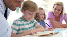 Parents Helping Children With Homework In Kitchen stock video footage