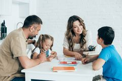 parents helping children with homework at table stock photography
