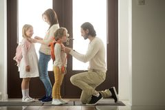 Parents helping children preparing go to school standing at hall. Caring parents helping happy kids put backpack on preparing go to school standing at house hall royalty free stock photography