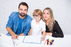 Parents helping cute little son with his homework Stock Image