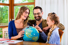 Parents helping daughter with homework assignment Stock Images