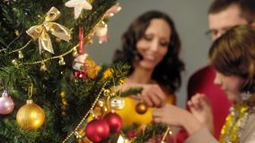 Parents helping daughter to decorate Christmas tree, magic moments, background stock photography