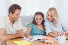 Parents helping her daughter doing her homework Royalty Free Stock Photos