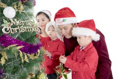 Parents helping sons to decorate a Christmas tree. Young parents helping their sons to decorate a Christmas tree in the studio, isolated on white background Stock Photo