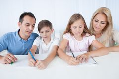 Parents Helping Their Children With Their Homework Stock Photos