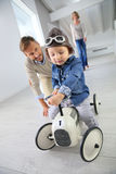 Parents helping their little boy riding toy car Stock Images