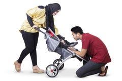 Parents heureux avec le bébé dans la voiture landau Photo stock
