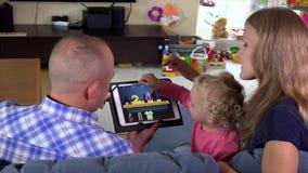 Parents heureux avec leur petite fille s'asseyant sur le sofa avec le comprimé banque de vidéos
