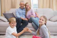 Parents heureux avec leurs enfants sur le plancher Photographie stock