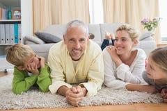 Parents heureux avec leurs enfants sur le plancher Image libre de droits