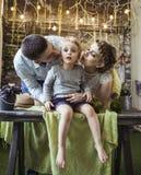 Parents heureux embrassant leur vieille fille de cinq ans Images stock