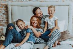 Parents heureux et deux enfants détendant ensemble photographie stock libre de droits
