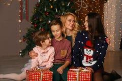 Parents heureux et enfants partageant des étreintes de Noël et regardant l'un l'autre Photos stock