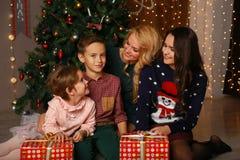 Parents heureux et enfants partageant des étreintes de Noël et regardant l'un l'autre Image stock