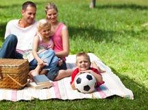 Parents heureux et enfants pique-niquant en stationnement Image stock