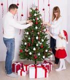 Parents heureux et petite fille décorant l'arbre de Noël à h Photo libre de droits