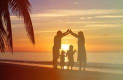 Parents heureux faisant à la maison pour des enfants au coucher du soleil Images libres de droits