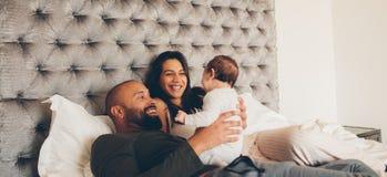 Parents heureux jouant avec leur fils nouveau-né sur le lit Images stock