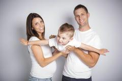 Parents heureux jouant l'avion avec leur garçon d'enfant d'isolement sur le fond blanc image stock