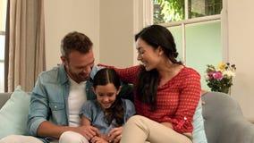 Parents heureux parlant avec leur fille sur le sofa clips vidéos