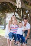 Parents heureux poussant leurs enfants sur une oscillation Image libre de droits
