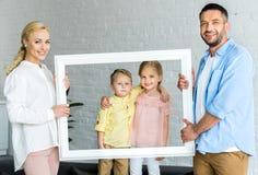 parents heureux tenant le cadre et petits enfants mignons photos stock