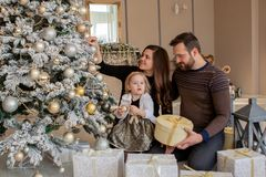 Parents and his little daughter decorating Christmas tree with toys and garlands stock image