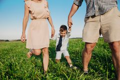 Parents hold baby`s hands. Happy young family of three smiling while spending free time outdoors royalty free stock photos