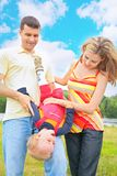 Parents hold child beneath by head. Parents hold child beneath by the head Royalty Free Stock Photo