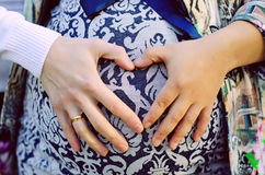 The parents hold hands on the tummy heart. The parents hold the tummy in the form of heart on a background of blue dress Royalty Free Stock Photography