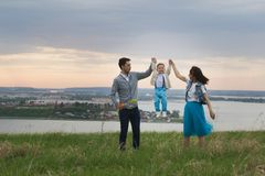 Parents hold their son`s hands and raise, the baby jumps, cloudy. Telephoto shot Stock Photo