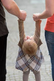 Parents holding daughter by the hands Stock Photography