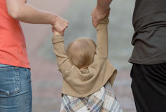 Parents holding daughter by the hands Royalty Free Stock Photography