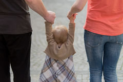 Parents holding daughter by the hands Stock Photo