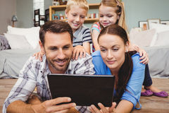 Parents holding digital tablet while kids sitting on their back Royalty Free Stock Image