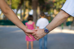 Parents Holding Hands with Kids in Front. Close up of holding hands, two kids in background Stock Photos