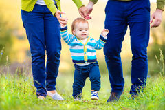 Parents holding hands of their son making first steps Stock Photo