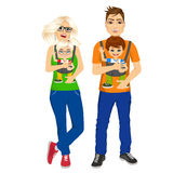 Parents holding holding their children with baby carrier Royalty Free Stock Photo