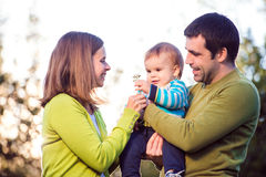Parents holding little son in their arms, sunny nature Royalty Free Stock Image